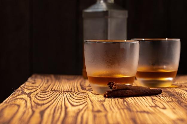 Dois copos de uísque e charutos na mesa de madeira fecham