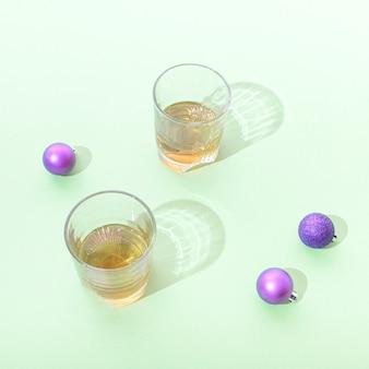 Dois copos de uísque em um fundo verde. bolas decorativas roxas de ano novo. conceito de comemorações de natal.