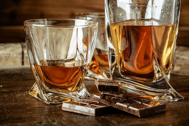 Dois copos de uísque ou uísque ou conhaque e pedaços de chocolate amargo