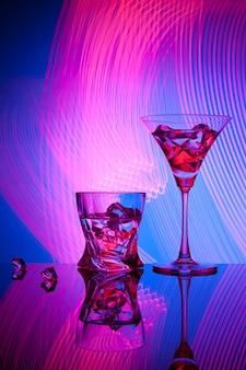 Dois copos de um cocktail martini whisky gelo, contra o azul de belos efeitos de luz.