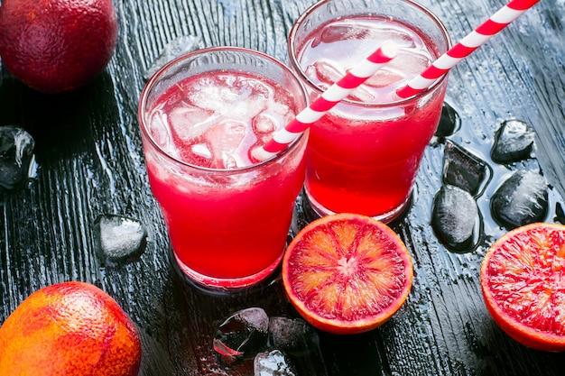 Dois copos de vermelho cítrico coquetel com gelo