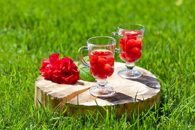 Dois copos de vidro com cerejas e água ficam em um carrinho de madeira com um crack e uma flor rosa vermelha em um gramado verde em um dia ensolarado de verão.