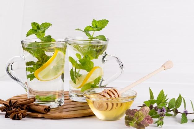 Dois copos de vidro de chá de hortelã fresca com limão e mel na mesa branca.