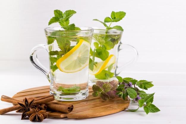 Dois copos de vidro de chá de hortelã fresca com limão na mesa branca.