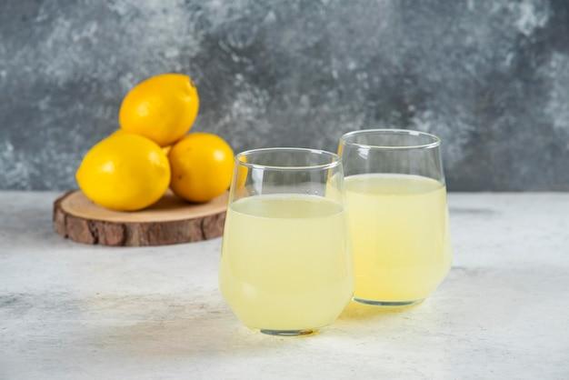 Dois copos de vidro de limonada com limões.