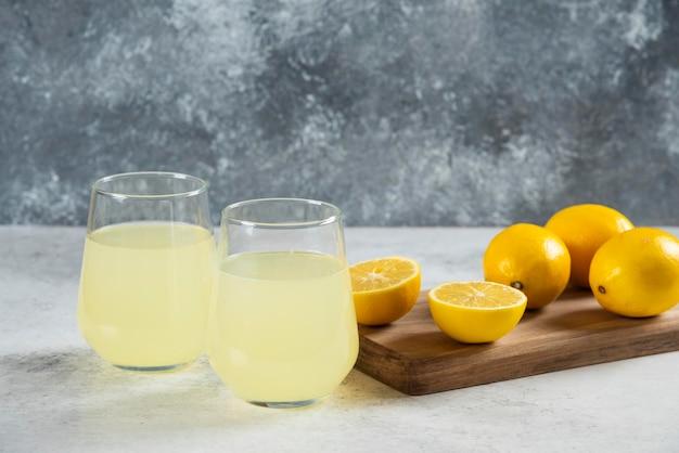 Dois copos de vidro de limonada fresca em uma placa de madeira.
