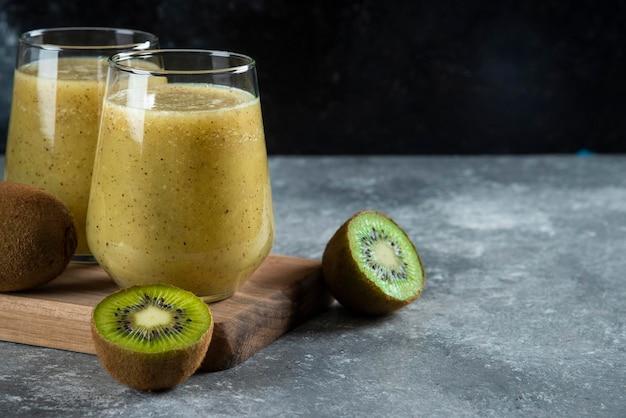 Dois copos de vidro de saboroso suco de kiwi na placa de madeira.