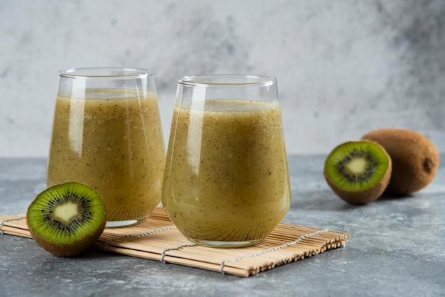 Dois copos de vidro de suco de kiwi fresco na folha de bambu.