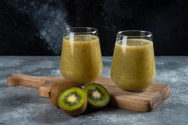Dois copos de vidro de suco de kiwi na placa de madeira.
