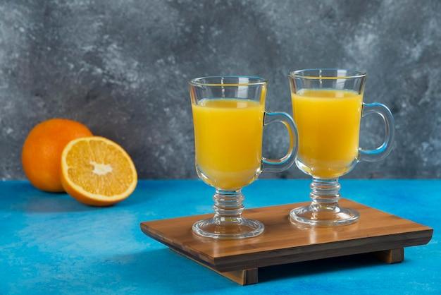 Dois copos de vidro de suco de laranja na placa de madeira.
