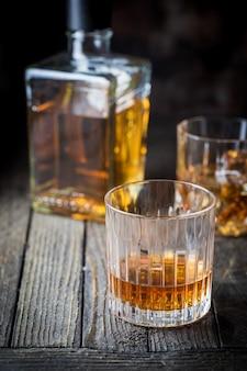Dois copos de vidro e uma garrafa de uísque na mesa de madeira escura