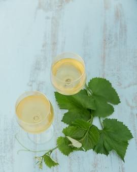 Dois copos de vinho branco com folhas de uva em azul claro