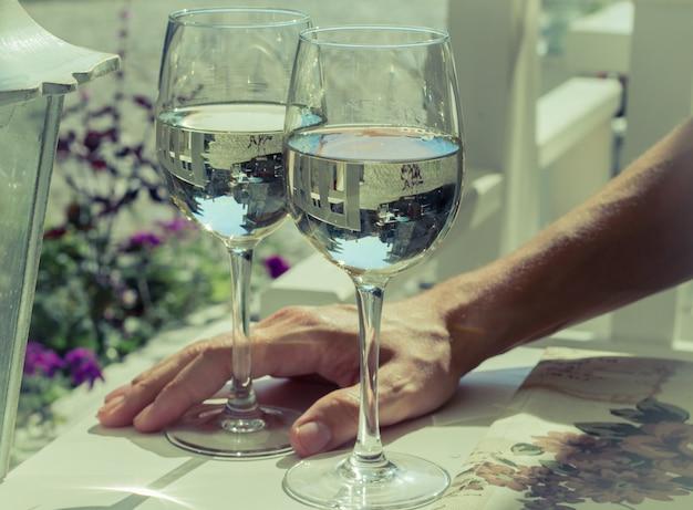 Dois copos de vinho branco com mão de homem