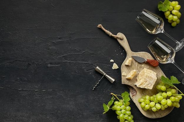 Dois copos de vinho branco e um saboroso prato de queijo com frutas em um prato de madeira na pedra preta