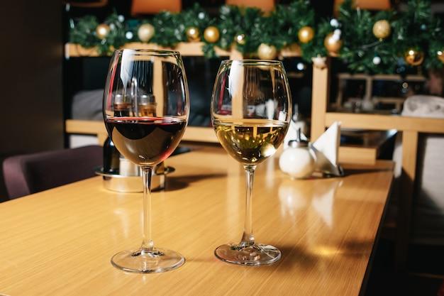 Dois copos de vinho branco e vermelho em pé sobre uma mesa com velas à luz do sol