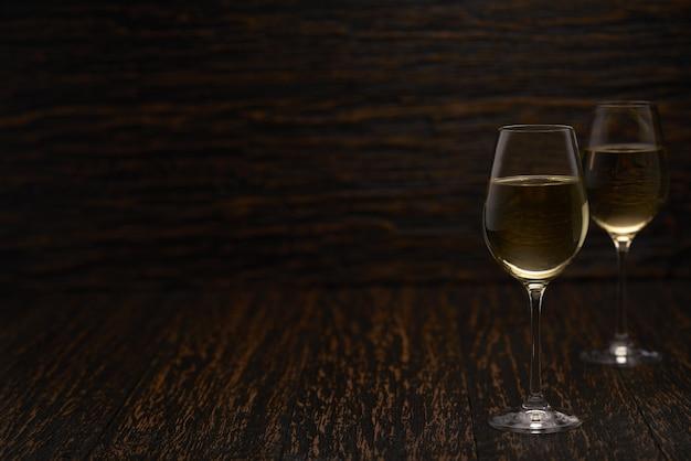 Dois copos de vinho branco em uma mesa de madeira preta, com espaço de cópia.
