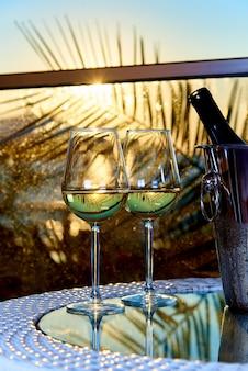 Dois copos de vinho branco frio sobre uma mesa de vidro na varanda