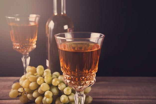 Dois copos de vinho branco, garrafa e cacho de uvas em pé sobre uma mesa de madeira