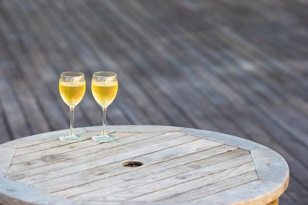 Dois copos de vinho branco saboroso ao pôr do sol na mesa de madeira