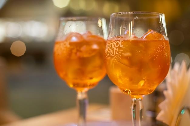 Dois copos de vinho com coquetel spritz ficam em uma mesa de madeira em um café, sob os raios do sol poente. bebida alcoólica italiana com laranja e gelo. close-up, foco seletivo