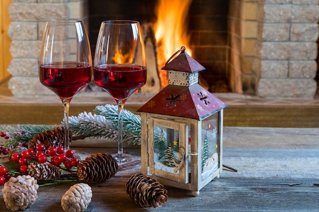 Dois copos de vinho e lanterna de natal perto da lareira, na casa de campo.