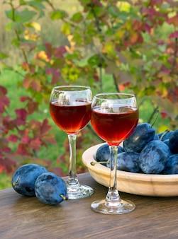 Dois copos de vinho e uma tigela cheia de ameixas. tiro horizontal ao ar livre.
