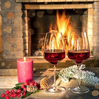 Dois copos de vinho e vela perto da lareira