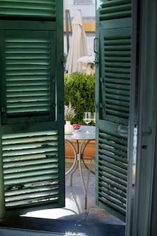 Dois copos de vinho, frutas frescas em uma mesa na varanda, vista através de persianas abertas