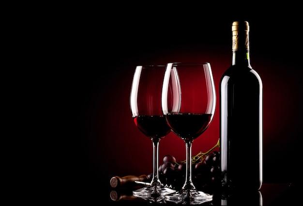 Dois copos de vinho, garrafa, uvas e saca-rolhas