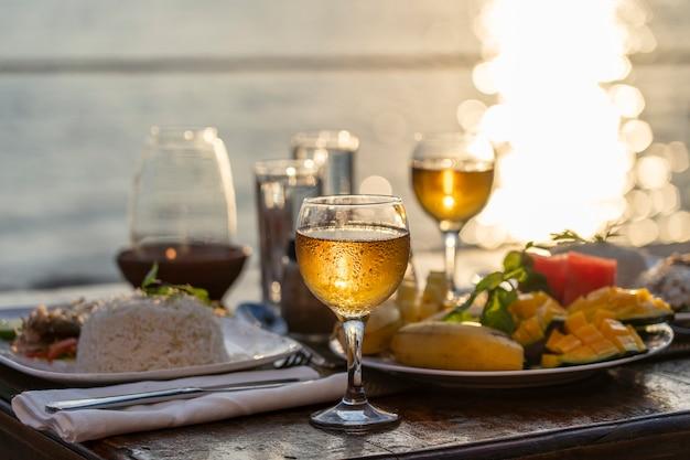 Dois copos de vinho na mesa de madeira perto do mar na praia tropical durante o pôr do sol