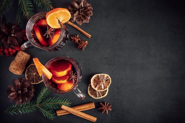 Dois copos de vinho quente com especiarias com frutas e especiarias em um fundo escuro. bebida de férias de aquecimento de inverno.