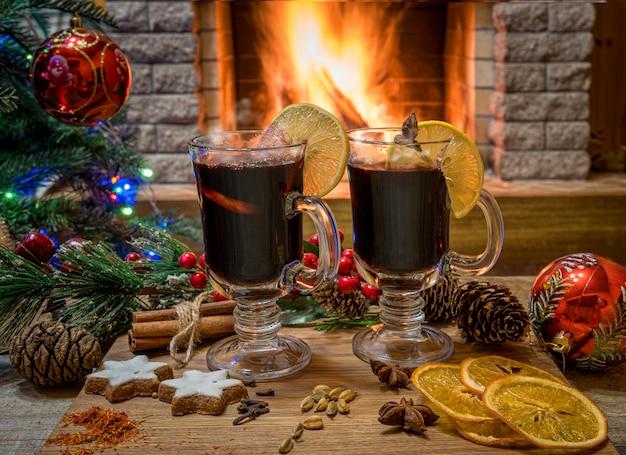 Dois copos de vinho quente em uma placa de madeira antes da árvore de natal decorada brinquedos e luzes de natal em frente a lareira em chamas.