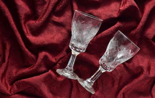 Dois copos de vinho retrô vazios em um fundo de seda vermelho. vista do topo.