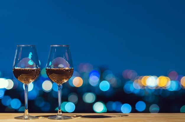Dois copos de vinho rosé com luz colorida de bokeh cidade do edifício no último piso.