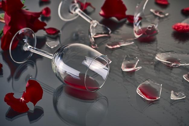 Dois copos de vinho tinto, caídos e quebrados, repousam sobre uma mesa de vidro com fragmentos de vidro e pétalas de rosas vermelhas frescas