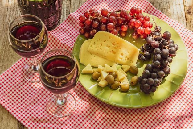 Dois copos de vinho tinto com um cacho de uvas, queijo e azeitonas.