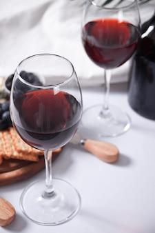 Dois copos de vinho tinto e prato com queijo variado, frutas e outros petiscos para festa