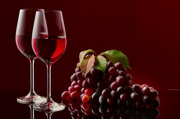 Dois copos de vinho tinto e um cacho de uvas em uma mesa lustrosa.
