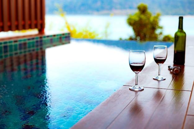 Dois copos de vinho tinto perto da piscina com uma vista espectacular sobre o mar