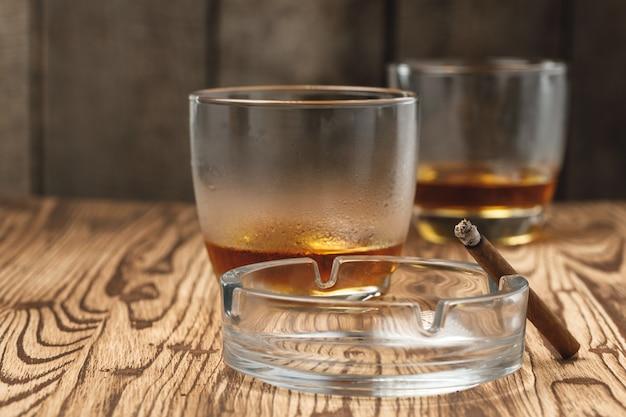 Dois copos de whisky com um cinzeiro vazio na mesa de madeira