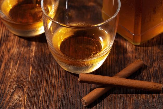 Dois copos de whisky e charutos na mesa de madeira