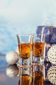 Dois copos de whisky ou bourbon com decoração de natal em um fundo claro bokeh. conceito de humor de uísque de feriados de ano novo, natal e inverno
