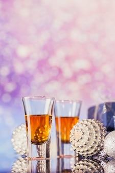 Dois copos de whisky ou bourbon com decoração de natal em um leve bokeh