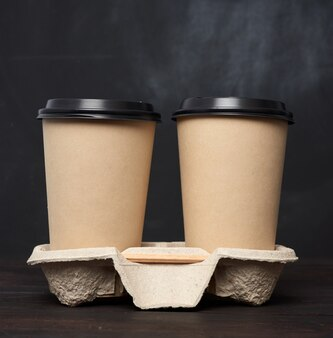 Dois copos descartáveis de papel pardo com uma tampa de plástico estão na bandeja sobre uma mesa de madeira