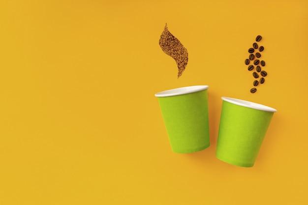 Dois copos descartáveis de papel verde para café decorados com grãos de café achatados sobre fundo amarelo