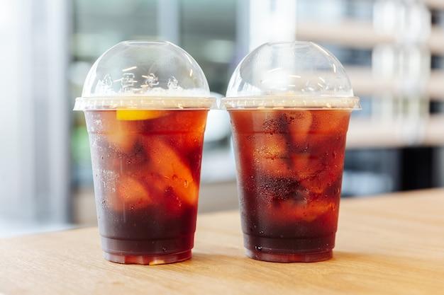 Dois copos do café frio da fermentação do nitro congelado com o limão na tabela de madeira com fundo do borrão.