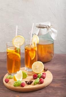 Dois copos e banco com kombuchá e rodelas de limão e framboesas em uma mesa de madeira.