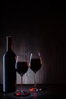 Dois copos e garrafa de vinho tinto na madeira