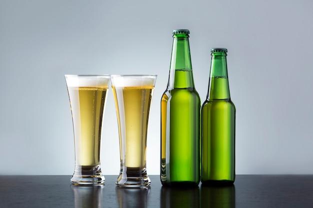 Dois copos e garrafas de cerveja no balcão do bar.