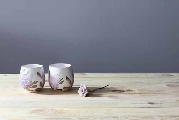 Dois copos e rosa na mesa de madeira